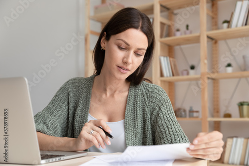 Leinwand Poster Close up focused young businesswoman working with documents in office, sitting a