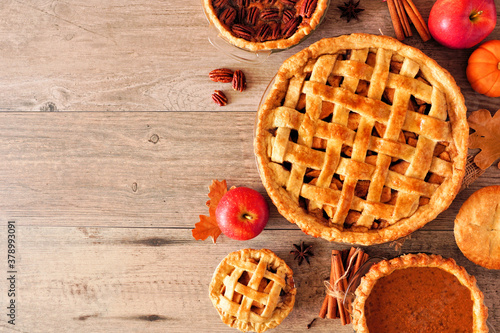 Assortment of homemade autumn pies. Apple, pecan and pumpkin. Top down view side border over a light wood background with copy space.