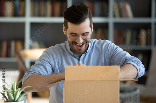 Fotografia Happy young Caucasian man feel excited unbox unpack cardboard box shopping online from home