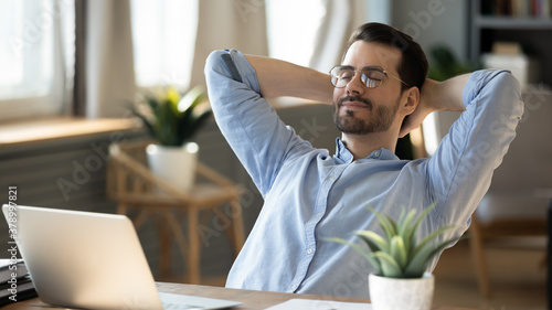 Fototapeta Calm millennial man in glasses sit relax at home office workplace take nap or daydream. Happy relaxed Caucasian young male rest in chair distracted from computer work, relieve negative emotions. obraz