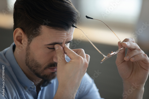 Canvas-taulu Close up of tired young man take off glasses massage eyes suffer from dizziness or blurry vision
