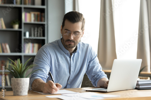 Concentrated young caucasian man in glasses sit at desk work on computer make notes. Focused serious male worker or freelancer busy at home office watch webinar on laptop, handwrite on paper.