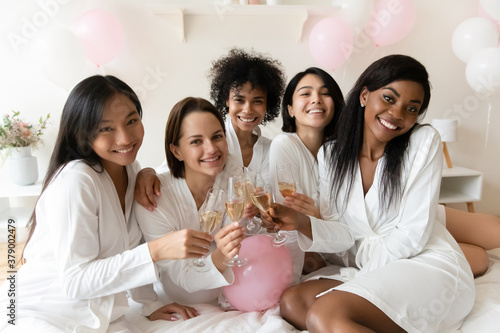 Portrait of smiling young mixed race pretty female best friends in white silk gowns, enjoying bachelorette hen pre-wedding party with sparkling wine, toasting saying wishes at luxury spa celebration.