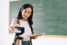 Smiling Asian Female Teacher Setting Camera Video With Recording Filming Working In Classroom Teaching Online In Blackboard To Student From Home.Remote During Quarantine,COVID-19 Epidemic.