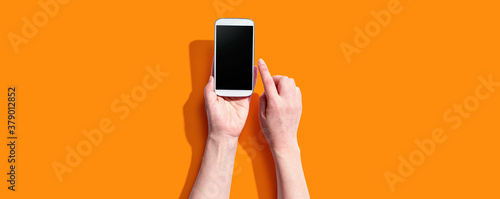 Fototapeta Person using a white smartphone from above obraz