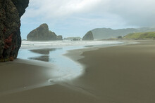 Water Washes Over The Sandy Beach Between The Sea Stacks On The Pacific Coast At Pistol River State Park, Oregon, USA