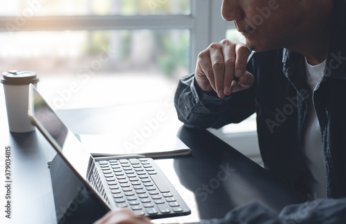 Obraz Pensive asian business man thinking while serious working on laptop computer from home office - fototapety do salonu