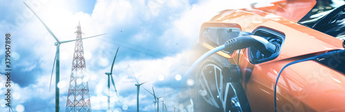 Fotografia Double exposure of electric car charge battery with wind turbine pole and blue sky blur bokeh on panoramic background