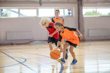 Kids In Bright Sportswear Playing Basketball In The Gym