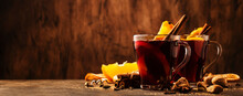 Hot Mulled Red Wine Cups With Spices And Fruits On Wooden Rustic Table. Traditional Autumn Hot Drink, Copy Space