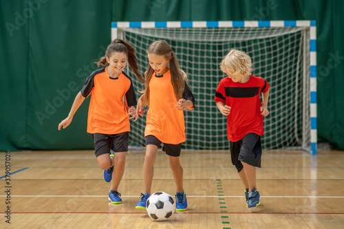 Fototapeta Kids in sportswear running after the ball obraz