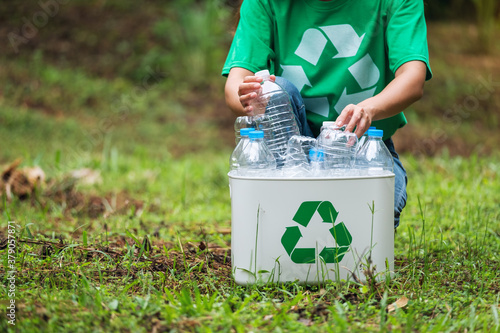 Fototapeta A woman collecting and putting plastic bottles into a recycle bin in the outdoors obraz
