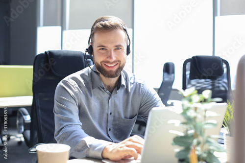 Smiling male call-center operator with headphones sitting at modern office, consulting online information in a laptop, looking up information in a file in order to be of assistance to the client Fototapet