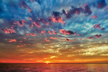 Fantastic Sunset Over The Black Sea. The Sun Was Almost Completely Hidden Behind The Glowing Scarlet Horizon. Pink Clouds In The Blue Sky. The Water Is Calm, Tinted Red.