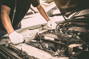 Close-up hands of auto mechanic are using the wrench to repair a car engine. Concepts of car care fix repair service and insurance.