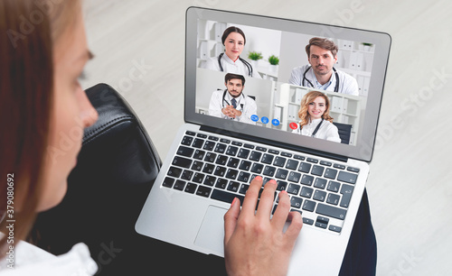 Fototapeta Young woman video chatting with medical doctors, top view obraz na płótnie