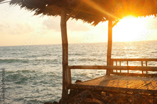 Fotomural View of a small hut near the ocean during sunset