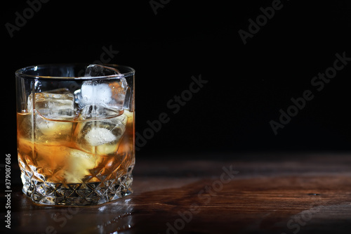 Obraz na plátně A glass of strong alcoholic drink with ice on a wooden bar counter