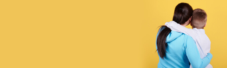 Brunette boy and mother sitting together, hugs, love, family. Isolated on yellow background, copy space template, banner.