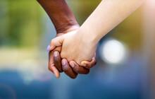 Interracial Couple Holding Han...