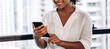 Leinwandbild Motiv Smiling beautiful professional business african american black woman working and using smartphone standing in office