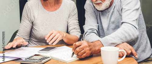 Fototapeta Senior couple reading documents and calculating bills to pay in living room at home.Retirement couple and loan bankruptcy money concept obraz