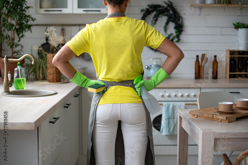 A maid in an apron, yellow rubber gloves and a yellow T-shirt stands with her back hands on hips Wallpaper Mural