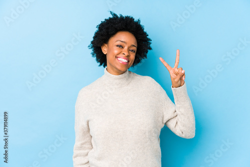 Middle aged african american woman against a blue background isolated showing victory sign and smiling broadly Fototapet