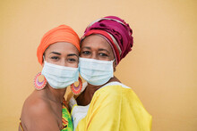 Beautiful African Mother And Daughter Hug Each Other While Wearing Protective Face Mask For Coronavirus - Family Love