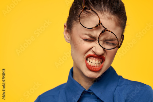 Fotografie, Obraz emotional woman with glasses on her face grimacing on yellow background
