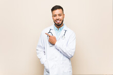 Young South-asian Doctor Man Smiling And Pointing Aside, Showing Something At Blank Space.