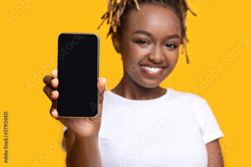 Fototapeta Cheerful black woman showing smartphone with blank screen obraz