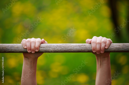 Photo Close-up of children's hands holding tightly to a stick