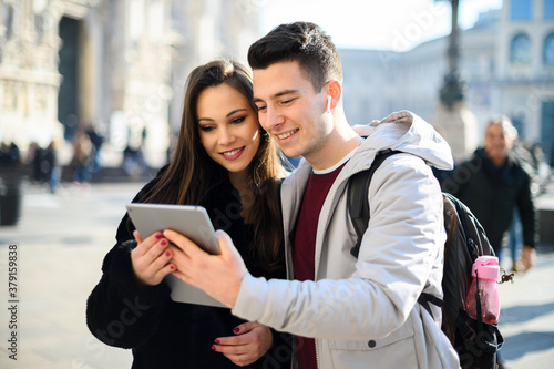 Young couple using a digital tablet outdoor while visiting a city Fototapet