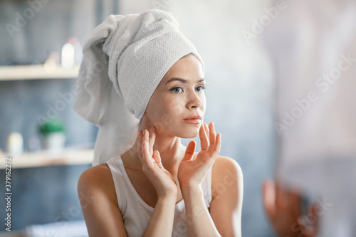 Obraz na plátně Serious lady in bath towel looking at her face in mirror at bathroom
