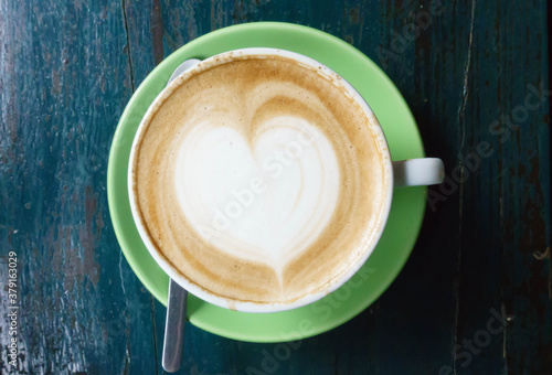 A cup of latte coffee with heart shape on green plate and silver spoon on a gree Fototapet