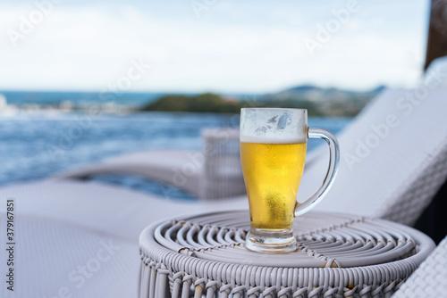 Fototapeta Fresh cold beer at rooftop swimming pool