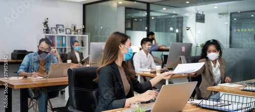 Fototapeta Asian business people group work in office with new normal lifestyle. obraz