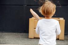 Blond Little Boy Facing The Wall, Holding Baguette, Outdoors