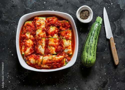 Fototapeta Preparing zucchini cannelloni with tomato sauce in a baking dish on a dark background, top view. Raw food ingredients obraz