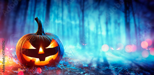 Pumpkin In Defocused Spooky Forest At Night - Halloween Concept