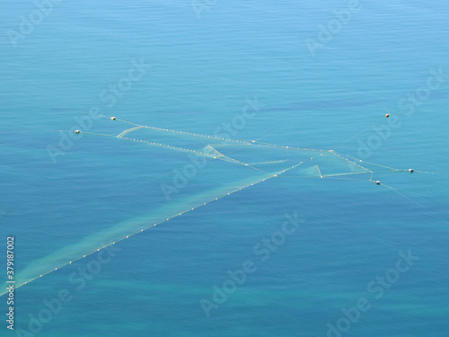 photograph of a large fishing net in the blue sea #379187002