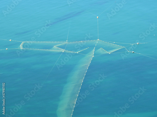 photograph of a large fishing net in the blue sea #379187012