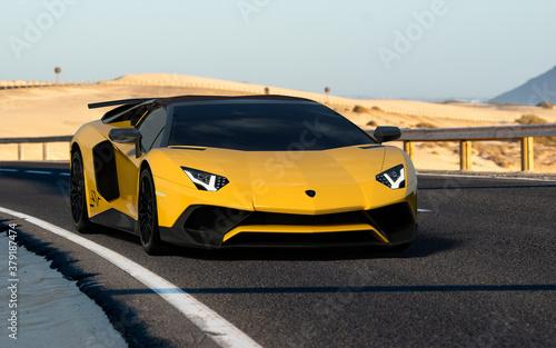 Lamborghini Aventador on a high-speed road across the dunes