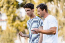 Father Gesturing And Talking With Teenager Son In Park