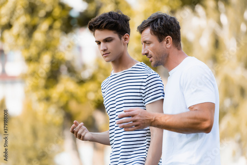 Obraz father gesturing and talking with teenager son in park - fototapety do salonu