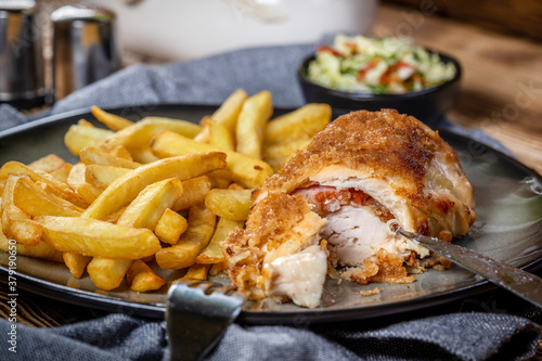 Fotografie, Obraz Fried chicken breast stuffed with bacon and cheese served with chips and salad