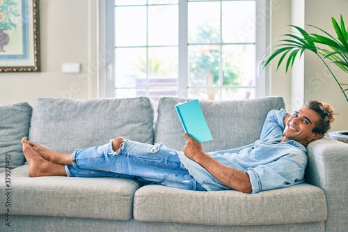 Young hispanic man smiling happy reading book laying on the sofa at home