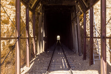 Dark Tracks Leading Into Train Tunnel With Opening In The Middle At The End