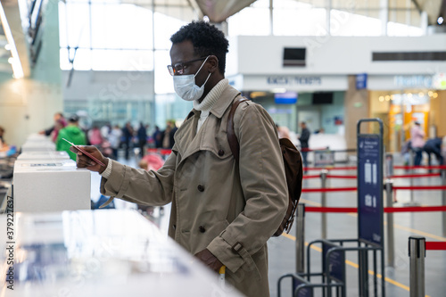 Obraz na plátně African American man stands at check-in counters at the airport terminal, giving passport to an officer